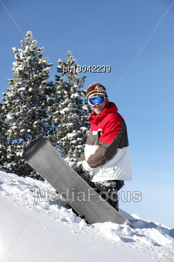 Snowboarder Struggling To Drag His Board Up The Mountain Stock Photo