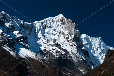 Snowbound Mountain Range And Blue Sky In Himalayas. Travel To Nepal Stock Photo