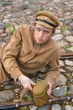 Soldier With Gun And Boiler In Uniform Of World War I, Resting On The Pavement. Costume Accord The Times Of World War I. Photo Made At Cinema City Cinevilla In Latvia. Cockade On The Hat Do Not Contai Stock Photo