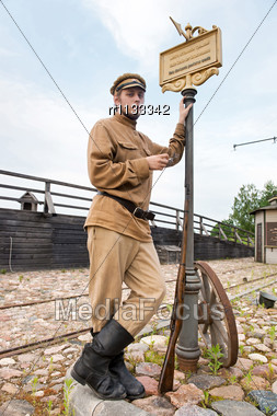 Soldier With A Gun In Uniform Of World War I, Smoking At Tram Stop. Costume Accord The Times Of World War I. Photo Made At Cinema City Cinevilla In Latvia Stock Photo