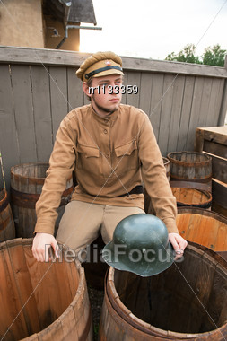 Soldier With A Helmet Sitting On The Butt.Costume Accord The Times Of World War I. Photo Made At Cinema City Cinevilla In Latvia Stock Photo