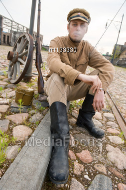 Soldier In Uniform Of World War I, Sit Down, Resting On The Pavement And Smoking. Costume Accord The Times Of World War I. Photo Made At Cinema City Cinevilla In Latvia. Cockade On The Hat Do Not Cont Stock Photo