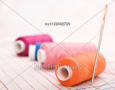 Spool Of Thread And Needle. Sew Accessories On Blurred Background Stock Photo