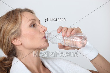 Sporty Woman Drinking Bottle Of Water Stock Photo