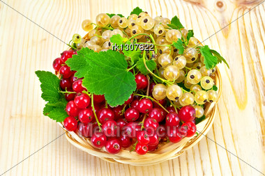 Sprigs Of Red And White Currants With Green Leaves In A Wicker Tray On A Light Wooden Board Stock Photo