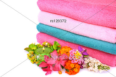 Stack Of Clean Colorful Towels With Candle And Flowers Stock Photo