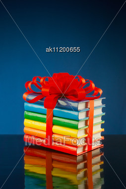 Stack Of Colorful Books Tied Up With Red Ribbon Stock Photo