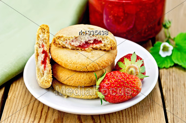 Stack Of Cookies Filled With Jam And Strawberries On A Plate, A Jar Of Strawberry Jam On The Background Of Wooden Boards Stock Photo