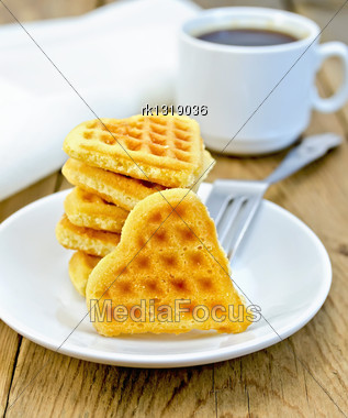 Stack Of Cookies In The Shape Of A Heart With A Fork On A White Plate, Cup And Napkin On A Background Of Wooden Boards Stock Photo