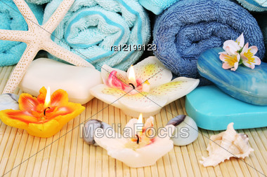 Stack Of Towels, Soaps, Candles, Stones, Flowers On Mat Background. Stock Photo