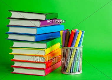 Stacks Of Colorful Books And Socket With Felt Pens Against Green Background Stock Photo