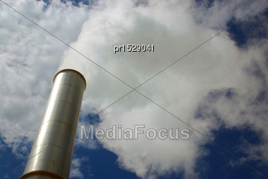 Steam Rising From Chimney On Industrial Site Stock Photo