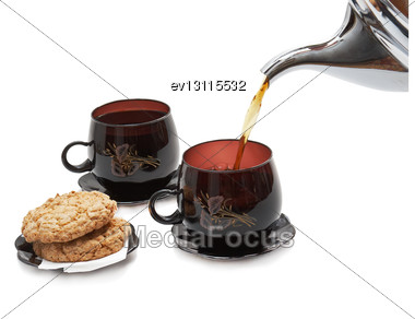 Still Life - Cookies, Two Cups And Pouring Tea. Isolated Stock Photo