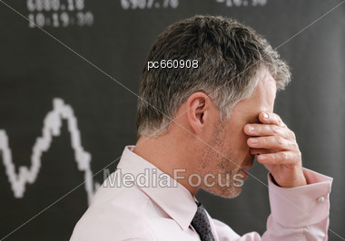Stock Broker in front of Stock Index, Devastated Stock Photo