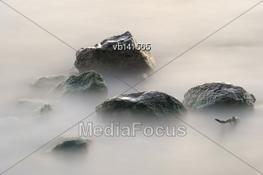 Stones In The Lake Early Morning, Wet From The Rolling Waves Stock Photo