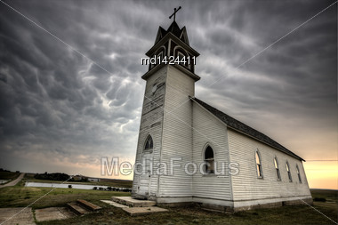 Storm Clouds Saskatchewan With Old Wooden Church In Foreground Stock Photo