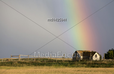 Storm Clouds Saskatchewan With Rainbow And Abandoned Farm Stock Photo