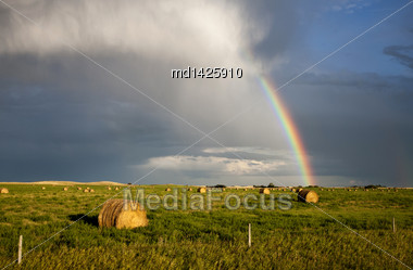 Storm Clouds Saskatchewan With Rainbow And Hay Bales Stock Photo
