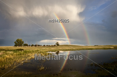 Storm Clouds Saskatchewan With Rainbow Reflection In Water Stock Photo
