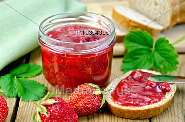Strawberry Jam In A Glass Jar, Bread, Strawberry With Leaves, Napkin, Knife On Background Wooden Plank Stock Photo
