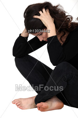 Stressed Brunette Sitting On The Floor Stock Photo