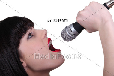 Stunning Woman Singing Into A Microphone Stock Photo
