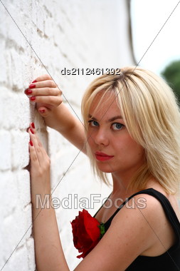 Stunningly Beautiful Young Blond Woman With Bright Blue Eyes Against Wall Stock Photo