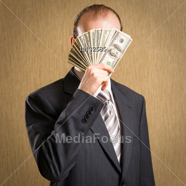 Stylish Businessman Concealing His Face With A Fistful Of American Dollar Bills Showing His Wealth And Success Or Hiding From Shady Dealings Stock Photo