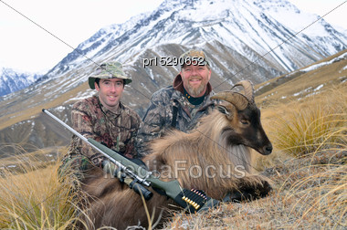 Successful Hunters With A Himalayan Tahr In The Southern Alps Of New Zealand Stock Photo