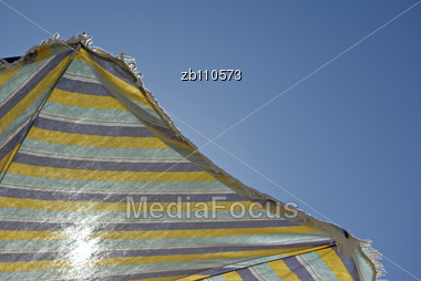 Sun Through Sunshade With Stripes Against Clear Blue Sky At Sunny Summer Day Stock Photo