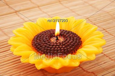 Sunflower Candle On Bamboo Background. Stock Photo