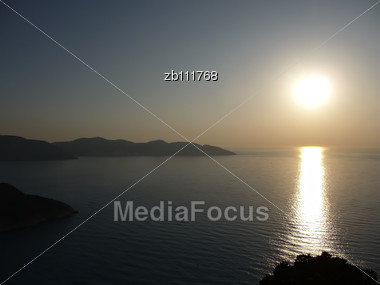 Sunset At One Of Greece Islands, Skyline With Local Hills And Sun Reflection In Sea Water Stock Photo