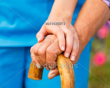 Supporting Hand From Doctor For Elderly With Parkinson's Disease Stock Photo