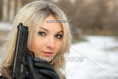 Sweet Woman With A Weapon In Winter Forest Stock Photo