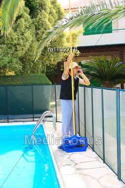 Swimming Pool Cleaner During His Work Stock Photo