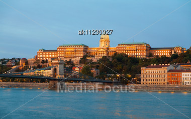 Szechenyi Chain Bridge In Budapest, Hungary At The Night Time With The Royal Palace Behind It Stock Photo