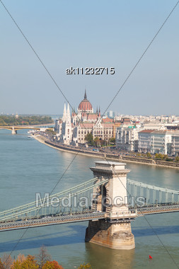 Szechenyi Suspension Bridge In Budapest, Hungary On A Sunny Day With The Parliament Building Behind It Stock Photo