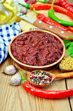 Tabasco Adjika In A Clay Cup, Different Hot Peppers, Garlic, Parsley, Fenugreek, Cloth, Oil On Wooden Board Stock Photo