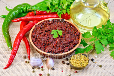 Tabasco Adjika In A Clay Cup, Different Hot Peppers, Garlic, Parsley, Fenugreek, Oil In A Carafe On The Sack Cloth Stock Photo
