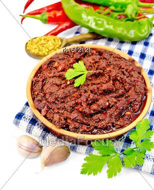 Tabasco Adjika In Clay Cup On A Napkin, Hot Pepper, Garlic, Parsley, Fenugreek Isolated On White Background Stock Photo