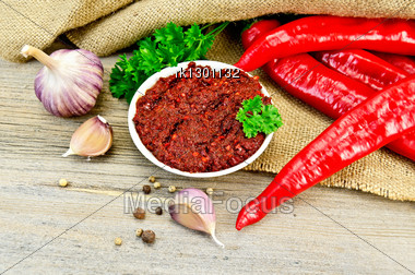 Tabasco In A White Cup, Fresh Red Peppers, Garlic, Peppercorns, Mustard Seeds On The Background Burlap And Wooden Planks Stock Photo