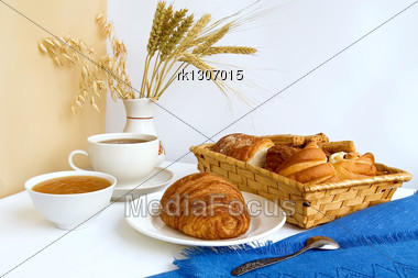 Table With A Cup Of Tea And Croissant On A Plate, Rolls In A Wicker Basket, Jam In A Bowl, Stalks Of Wheat, Oats And Rye In A Vase, Blue Cloth, A Teaspoon Against A Background Of White And Beige Curta Stock Photo
