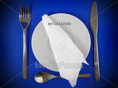 Table Serving-knife,plate,fork And Silk Napkin On Blue Colour Background Stock Photo