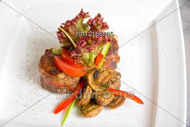 Tasty Beef Steak Grilled In A Cast-iron Ribbed Fry Pan With Bacon Decorated With Vegetables And Roasted Mushrooms Stock Photo
