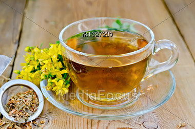 Tea In A Glass Cup, A Metal Filter For Tea With Dried Flowers Tutsan, Hypericum Fresh Flowers On The Background Of Wooden Boards Stock Photo