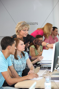 Teacher Helping Her Students Stock Photo