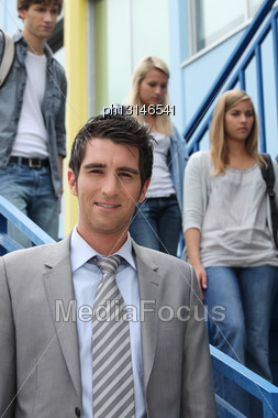 Teacher Looking At Us And Three Students In The Background Stock Photo