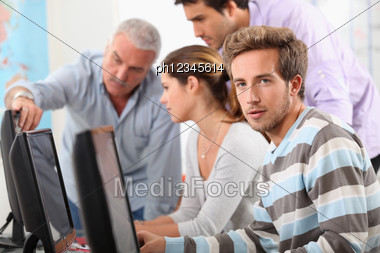 Teacher And Students Gathered Around Computer Screen Stock Photo