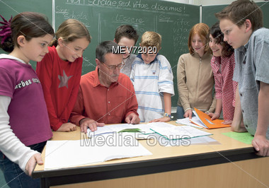 Teacher With Students Standing Around Desk Stock Photo