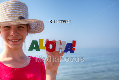 Teen Girl At A Beach Holding Word 'Aloha' Stock Photo